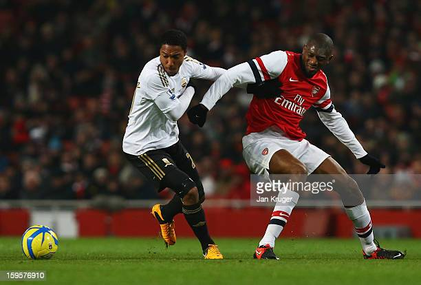 Jonathan de Guzman of Swansea City holds off Abou Diaby of Arsenal during the FA Cup with Budweiser Third Round Replay match between Arsenal and...