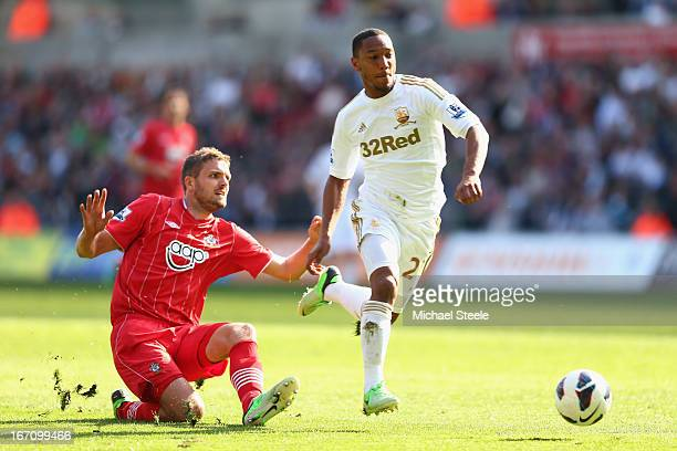 Jonathan de Guzman of Swansea City hurdles the challenge of Jos Hooiveld of Southampton during the Barclays Premier League match between Swansea City...