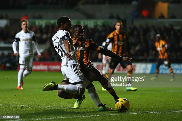 Jonathan de Guzman of Swansea City is challenged by Maynor Figueroa of Hull City during the Barclays Premier League match between Swansea City and...