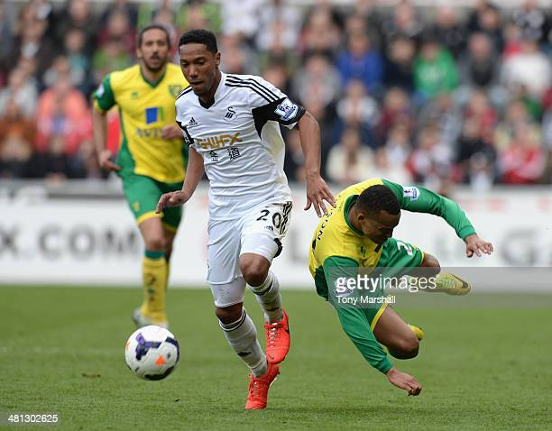 Jonathan De Guzman of Swansea City wins the ball from Martin Olsson of Norwich City during the Barclays Premier League match between Swansea City and...
