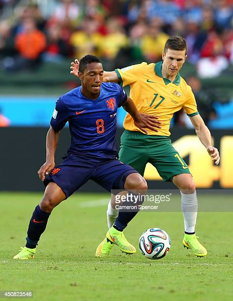 Jonathan de Guzman of the Netherlands and Matt McKay of Australia compete for the ball during the 2014 FIFA World Cup Brazil Group B match between...