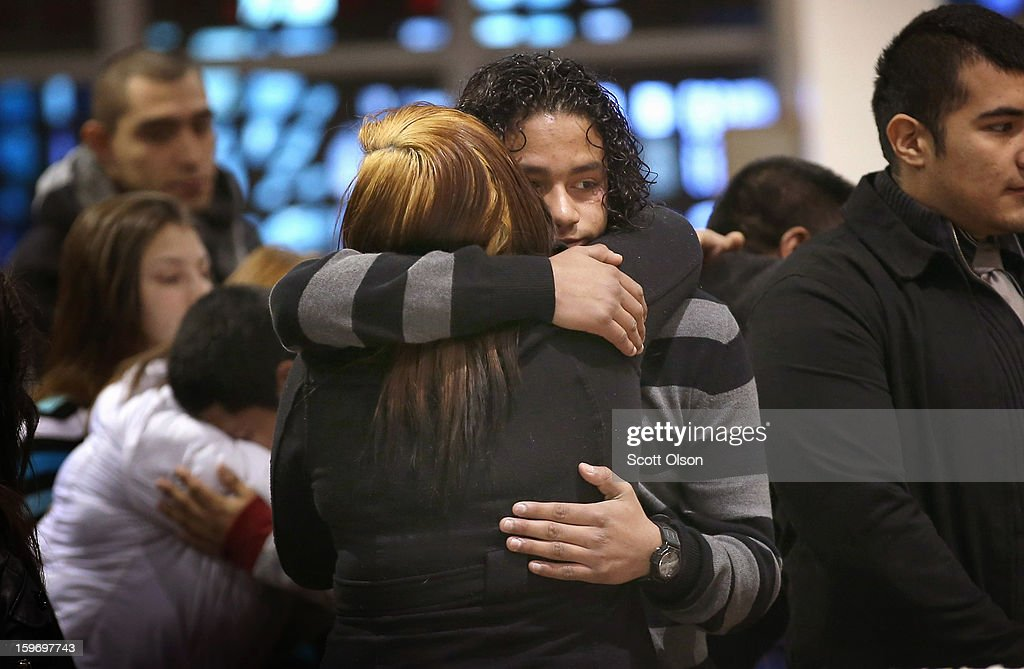 Jonathan Dorantes (R) gets a hug from a family friend during a funeral mass for his brother Rey on January 18, 2013 in Chicago, Illinois. Rey Dorantes, 14, died after being shot six times while he was sitting on the front porch of his home while talking on the phone on January 11. Dorantes's murder was the 21st homicide recorded in Chicago for 2013, a city which saw more than 500 homicides in 2012.