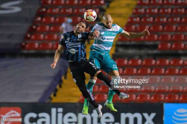 Jonathan Dos Santos jumps for a header against Matheus Doria of Santos during the 14th round match between Queretaro and Santos Laguna as part of the...