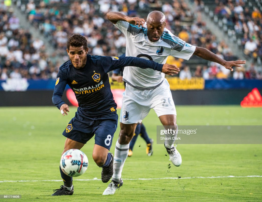 Jonathan dos Santos #8 of Los Angeles Galaxy battles Collen Warner #26 of Minnesota United during the Los Angeles Galaxy's MLS match against Minnesota United at the StubHub Center on October 15, 2017 in Carson, California. Los Angeles Galaxy won the match 3-0