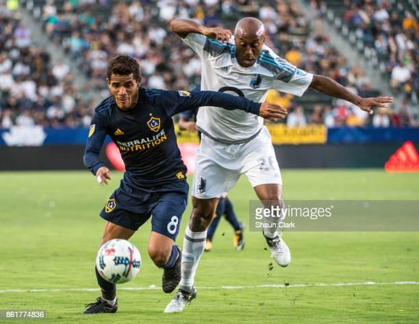 Jonathan dos Santos of Los Angeles Galaxy battles Collen Warner of Minnesota United during the Los Angeles Galaxy's MLS match against Minnesota...