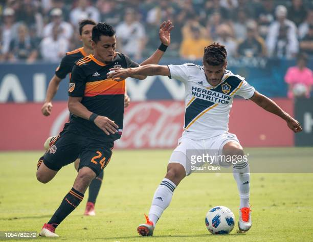 Jonathan dos Santos of Los Angeles Galaxy battles Darwin Ceren of Houston Dynamo during the Los Angeles Galaxy's MLS match against Houston Dynamo at...