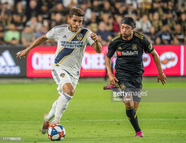 Jonathan dos Santos of Los Angeles Galaxy goes past Lee Nguyen of Los Angeles FC during the MLS Western Conference Semi-final between Los Angeles FC...