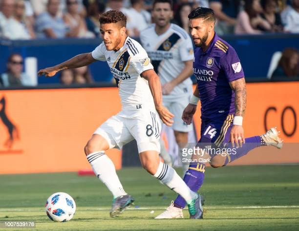 Jonathan dos Santos of Los Angeles Galaxy moves the ball past Dom Dwyer of Orlando City at the StubHub Center on July 29 2018 in Carson California...