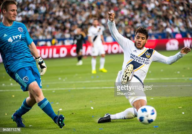 Jonathan dos Santos of Los Angeles Galaxy races in on Adrian Zendejas of Sporting Kansas City during the Los Angeles Galaxy's MLS match against...