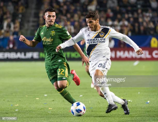 Jonathan dos Santos of Los Angeles Galaxy races in on goal as Cristhian Paredes of Portland Timbers defends during the Los Angeles Galaxy's MLS match...
