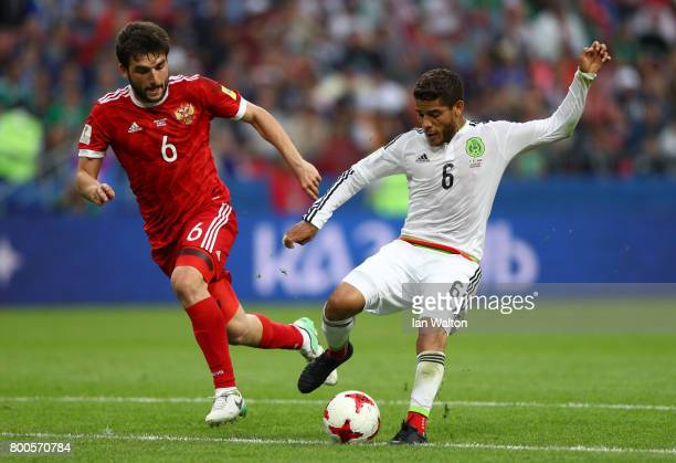 Jonathan Dos Santos of Mexico and Georgy Dzhikya of Russia compete for the ball during the FIFA Confederations Cup Russia 2017 Group A match between...