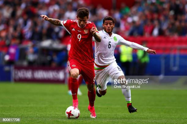 Jonathan Dos Santos of Mexico in action with Fedor Smolov of Russia during the FIFA Confederations Cup Russia 2017 Group A match between Mexico and...