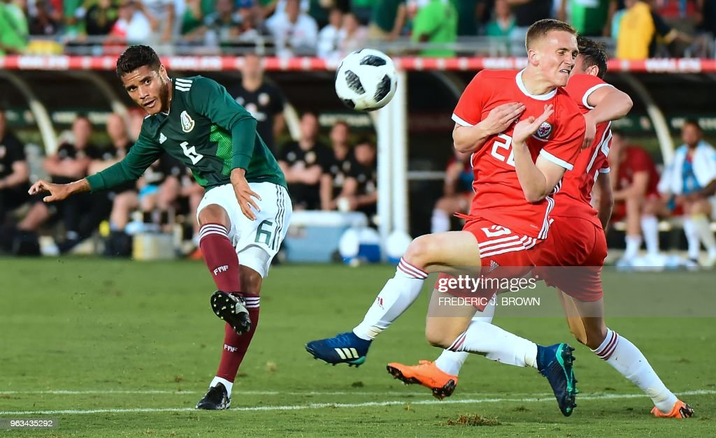 Jonathan dos Santos of Mexico (L) shoots under pressure from Matt Smith (C) and Tom Lockyer (R) of Wales during their international soccer friendly at the Rose Bowl in Pasadena, California on May 28, 2018. - The game ended 0-0.