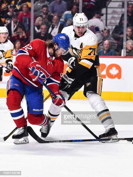 Jonathan Drouin of the Montreal Canadiens and Evgeni Malkin of the Pittsburgh Penguins battle for the puck during the NHL game at the Bell Centre on...