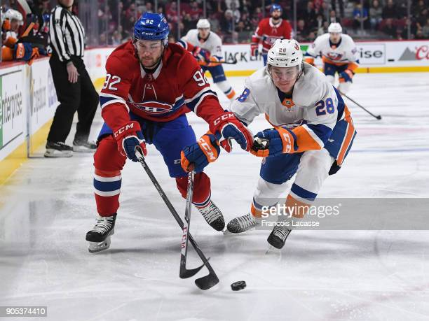 Jonathan Drouin of the Montreal Canadiens fights for the puck against Sebastian Aho of the New York Islanders in the NHL game at the Bell Centre on...