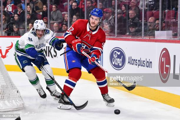 Jonathan Drouin of the Montreal Canadiens skates the puck against Loui Eriksson of the Vancouver Canucks during the NHL game at the Bell Centre on...