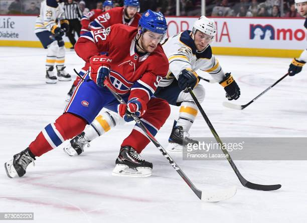 Jonathan Drouin of the Montreal Canadiens skates with the puck under pressure from Johan Larsson of the Buffalo Sabres in the NHL game at the Bell...