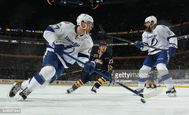 Jonathan Drouin of the Tampa Bay Lightning skates with the puck around Luke Witkowski watched by Sam Reinhart of the Buffalo Sabres during an NHL...