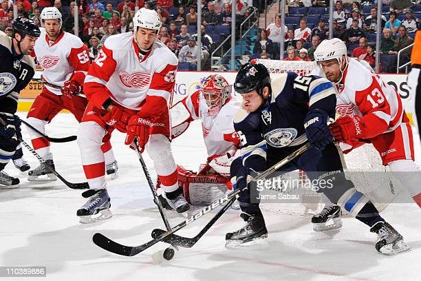 Jonathan Ericsson and Pavel Datsyuk both of the Detroit Red Wings work to knock the puck away from Derek Dorsett of the Columbus Blue Jackets during...
