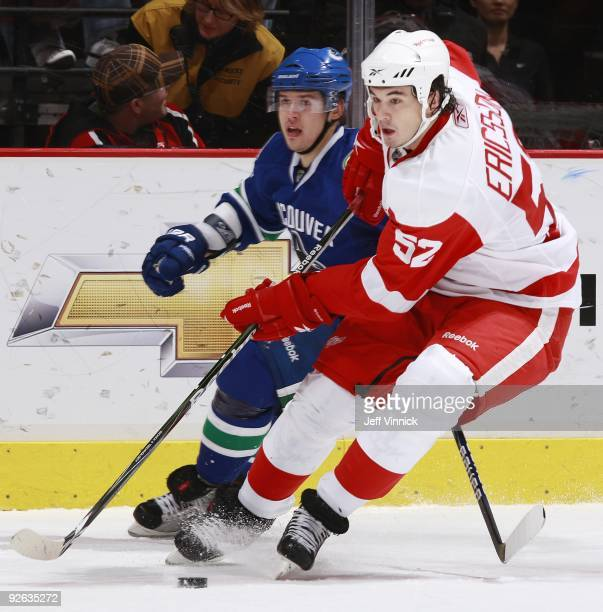 Jonathan Ericsson of the Detroit Red Wings and Sergei Shirokov of the Vancouver Canucks battle for the puck during their game at General Motors Place...