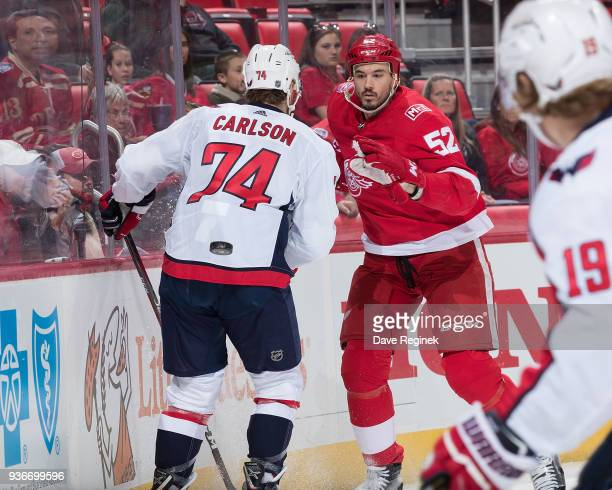 Jonathan Ericsson of the Detroit Red Wings battles along the boards for the puck with John Carlson of the Washington Capitals during an NHL game at...