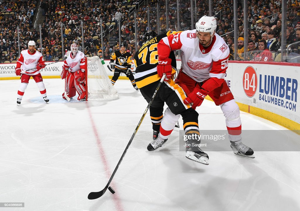 Jonathan Ericsson #52 of the Detroit Red Wings handles the puck against Patric Hornqvist #72 of the Pittsburgh Penguins at PPG Paints Arena on January 13, 2018 in Pittsburgh, Pennsylvania.
