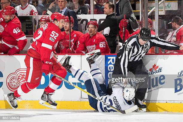 Jonathan Ericsson of the Detroit Red Wings skates behind Nikita Soshnikov of the Toronto Maple Leafs as he crashes into linesman Scott Driscoll...
