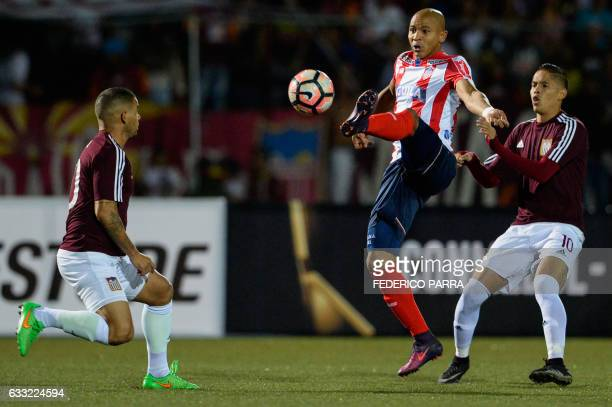 Jonathan Estrada of Colombia's Junior vies for ball with Aquiles Ocanto and Juan Colina of Venezuela's Carabobo FC during their 2017 Copa...