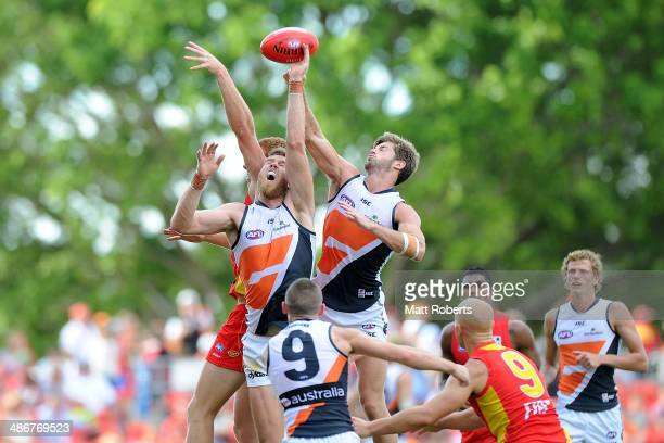 Jonathan Giles and Callan Ward of the Giants compete for the ball with Rory Thompson of the Suns during the round six AFL match between the Gold...