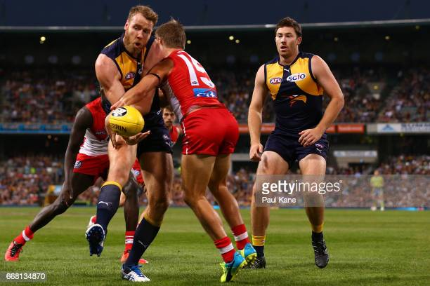Jonathan Giles of the Eagles handballs against Kieren Jack of the Swans during the round four AFL match between the West Coast Eagles and the Sydney...