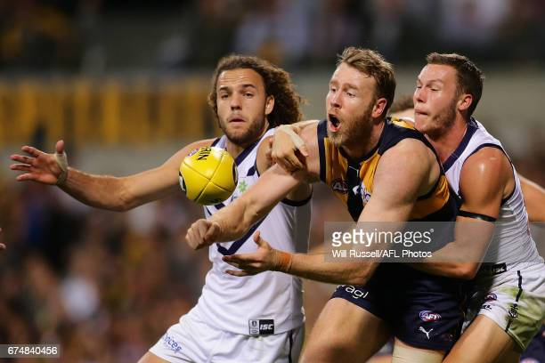 Jonathan Giles of the Eagles tries to handpass the ball under pressure from Griffin Logue and Ed Langdon of the Dockers during the round six AFL...