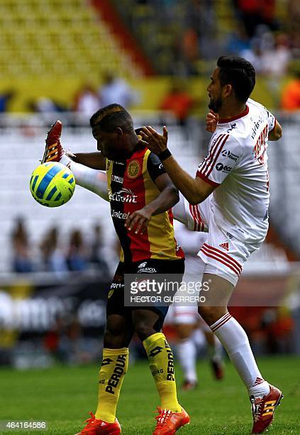 Jonathan Gonzales of Leones Negros vies for the ball with Jesus Chavez of Tijuana during their Mexican Clausura 2015 tournament football match at...