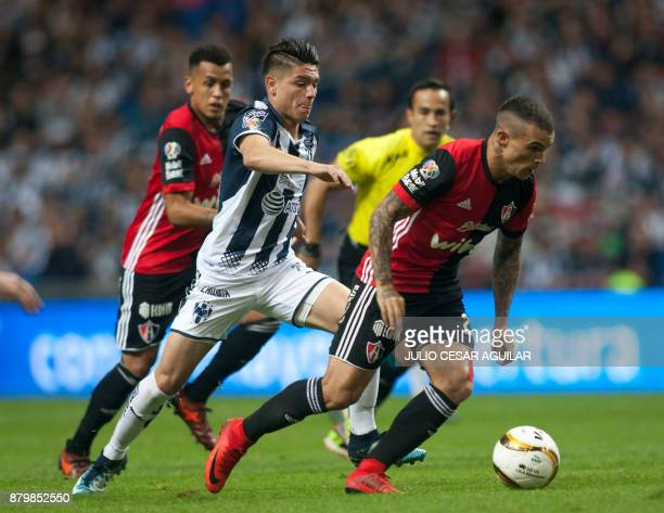 Jonathan Gonzalez of Monterrey vies for the ball with Christian Tabo of Atlas during their quarter final Mexican Apertura 2017 tournament football...