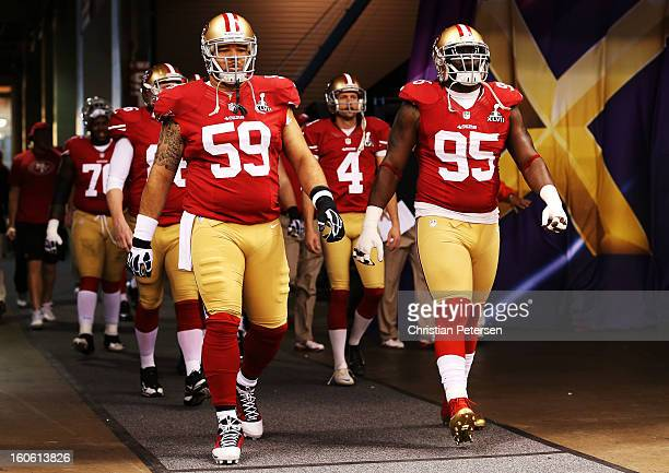 Jonathan Goodwin and Ricky Jean Francois of the San Francisco 49ers walk out of the tunnel to take the field against the Baltimore Ravens during...