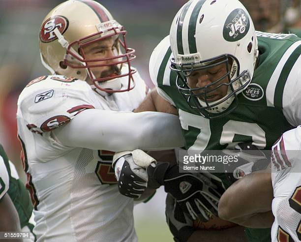 Jonathan Goodwin of the New York Jets blocks Jeff Ulbricht of the San Francisco 49ers in the game on October 17 2004 at Giants Stadium in East...