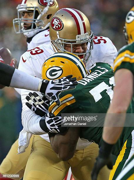 Jonathan Goodwin of the San Fransico 49ers blocks Mike Daniels of the Green Bay Packers during an NFC Wild Card Playoff game at Lambeau Field on...