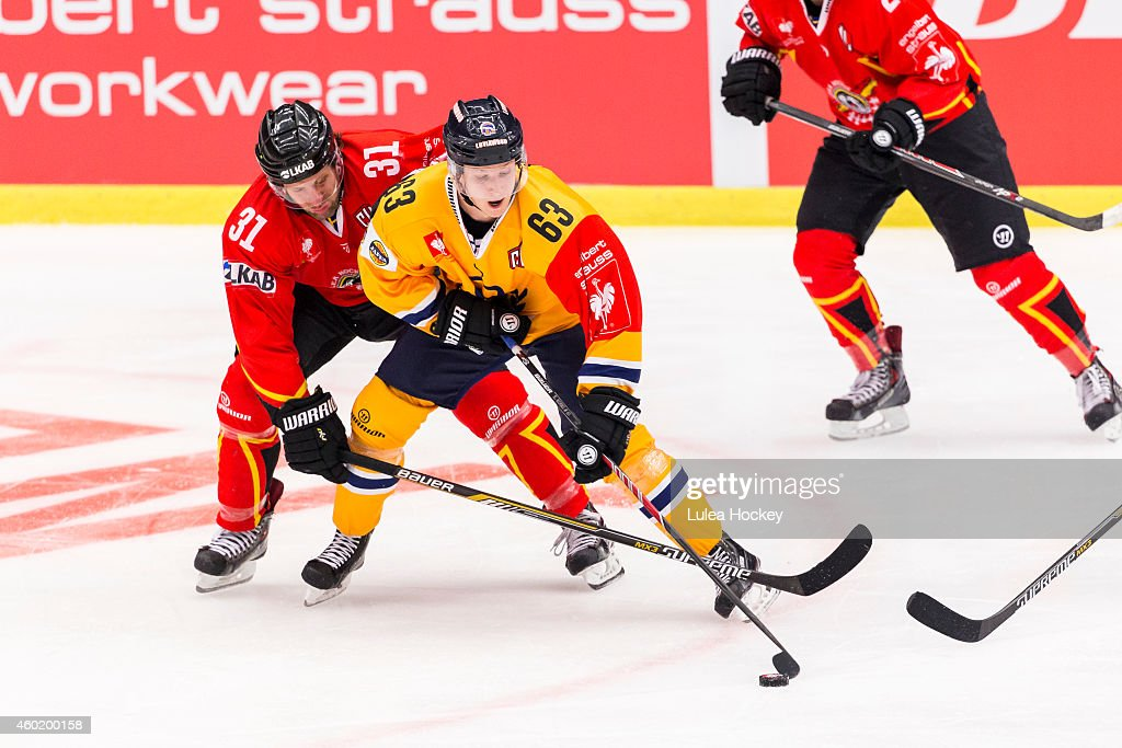 Jonathan Granstrom #31 of Lulea Hockey and Eetu Koski #63 of Lukko Rauma whit the puck during the Champions Hockey League quarter final second leg game between Lulea Hockey and Lukko Rauma at Coop Norrbotten Arena on December 9, 2014 in Lulea, Sweden.
