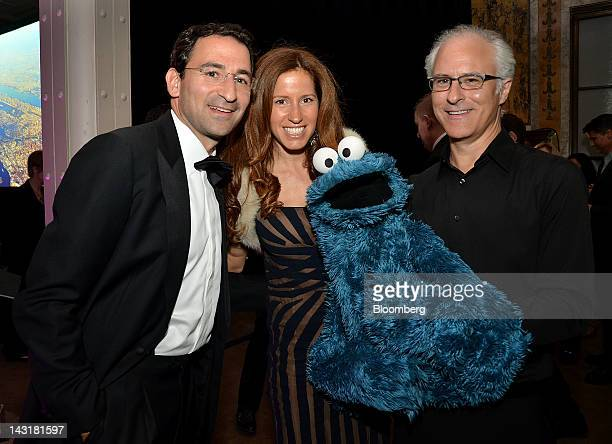 Jonathan Gray senior managing director of Blackstone Group LP from left wife Mindy Gray and Cookie Monster puppeteer David Rudman stand for a...