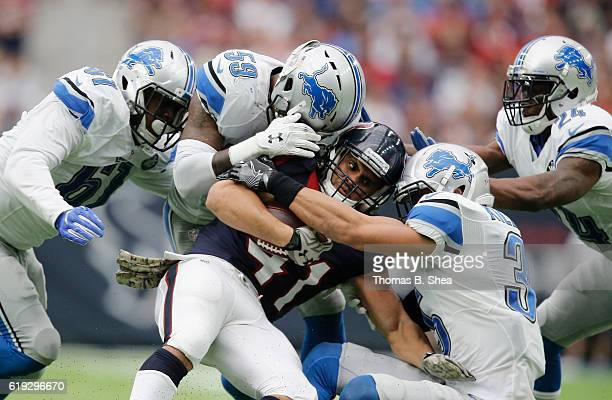 Jonathan Grimes of the Houston Texans is wrapped up by Tahir Whitehead of the Detroit Lions and Miles Killebrew in the fourth quarter at NRG Stadium...