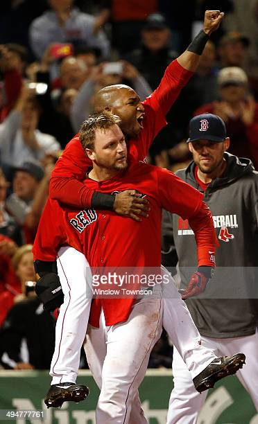 Jonathan Herrera of the Boston Red Sox jumps on the back of AJ Pierzynski after Pierzynski's game winning RBI triple during the tenth inning of their...