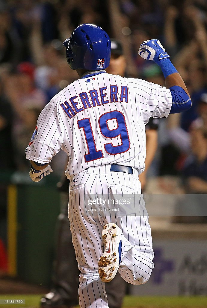 Jonathan Herrera #19 of the Chicago Cubs celebrates as he runs to home plate for the game-winning run in the bottom outfield the 9th inning against the Washington Nationals at Wrigley Field on May 26, 2015 in Chicago, Illinois. The Cubs defeated the Nationals 3-2.