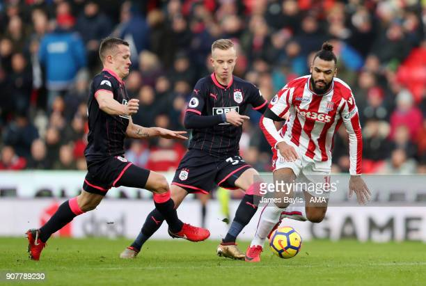 Jonathan Hogg and Florent Hadergjonaj of Huddersfield Town and Eric Maxim ChoupoMoting of Stoke City during the Premier League match between Stoke...