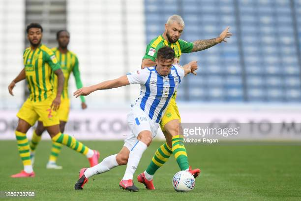 Jonathan Hogg of Huddersfield Town battles for possession with Charlie Austin of West Bromwich Albion during the Sky Bet Championship match between...