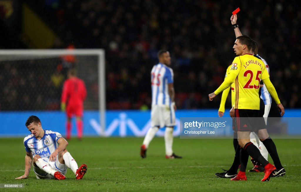 Jonathan Hogg of Huddersfield Town by referee Michael Oliver during the Premier League match between Watford and Huddersfield Town at Vicarage Road on December 16, 2017 in Watford, England.