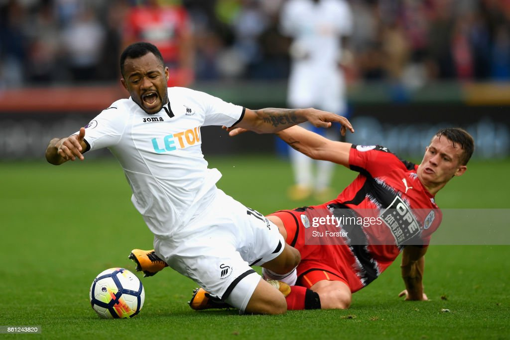 Jonathan Hogg of Huddersfield Town fouls Jordan Ayew of Swansea City during the Premier League match between Swansea City and Huddersfield Town at Liberty Stadium on October 14, 2017 in Swansea, Wales.