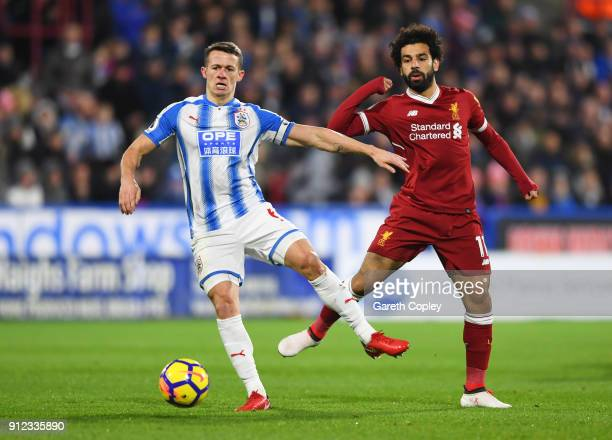 Jonathan Hogg of Huddersfield Town holds off Mohamed Salah of Liverpool during the Premier League match between Huddersfield Town and Liverpool at...