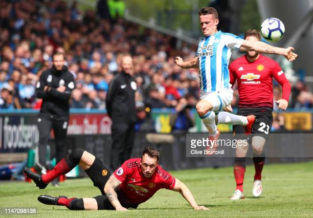 Jonathan Hogg of Huddersfield Town jumps a challenge from Phil Jones of Manchester United during the Premier League match between Huddersfield Town...