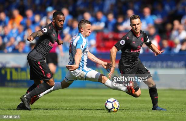 Jonathan Hogg of Huddersfield Town tries to beat Alexandre Lacazette and Aaron Ramsey of Arsenal during the Premier League match between Huddersfield...