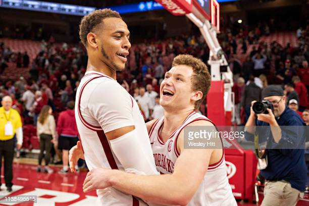 Jonathan Holmes hugs Daniel Gafford of the Arkansas Razorbacks after a game against the Alabama Crimson Tide at Bud Walton Arena on March 9 2019 in...