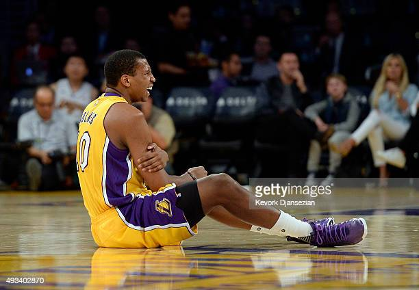 Jonathan Holmes of the Los Angeles Lakers holds his right shoulder after colliding with Allen Crabbe of the Portland Trail Blazers during the first...